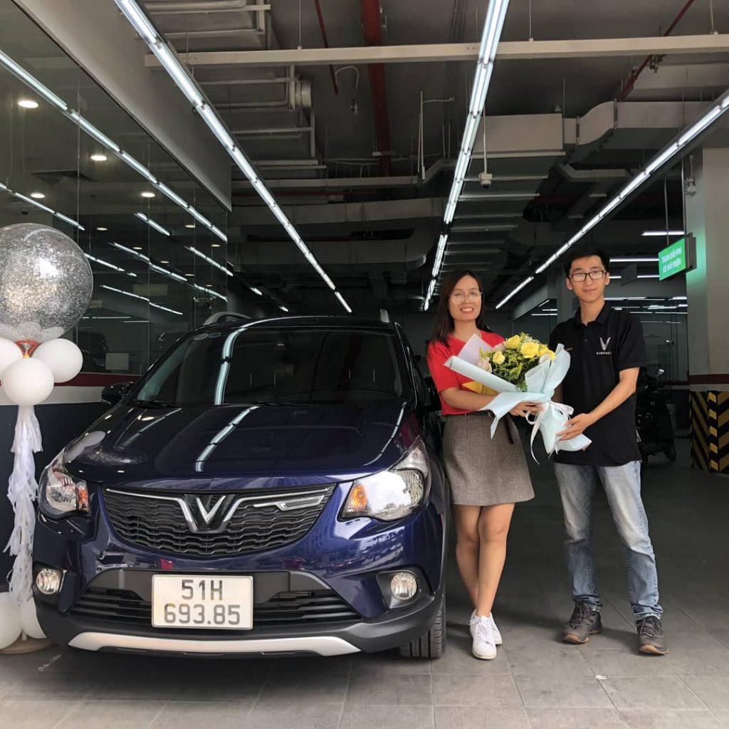 nhân viên kinh doanh vinfast thảo điền trao tặng hoa cho khách hàng trong lễ bàn giao xe vinfast fadil