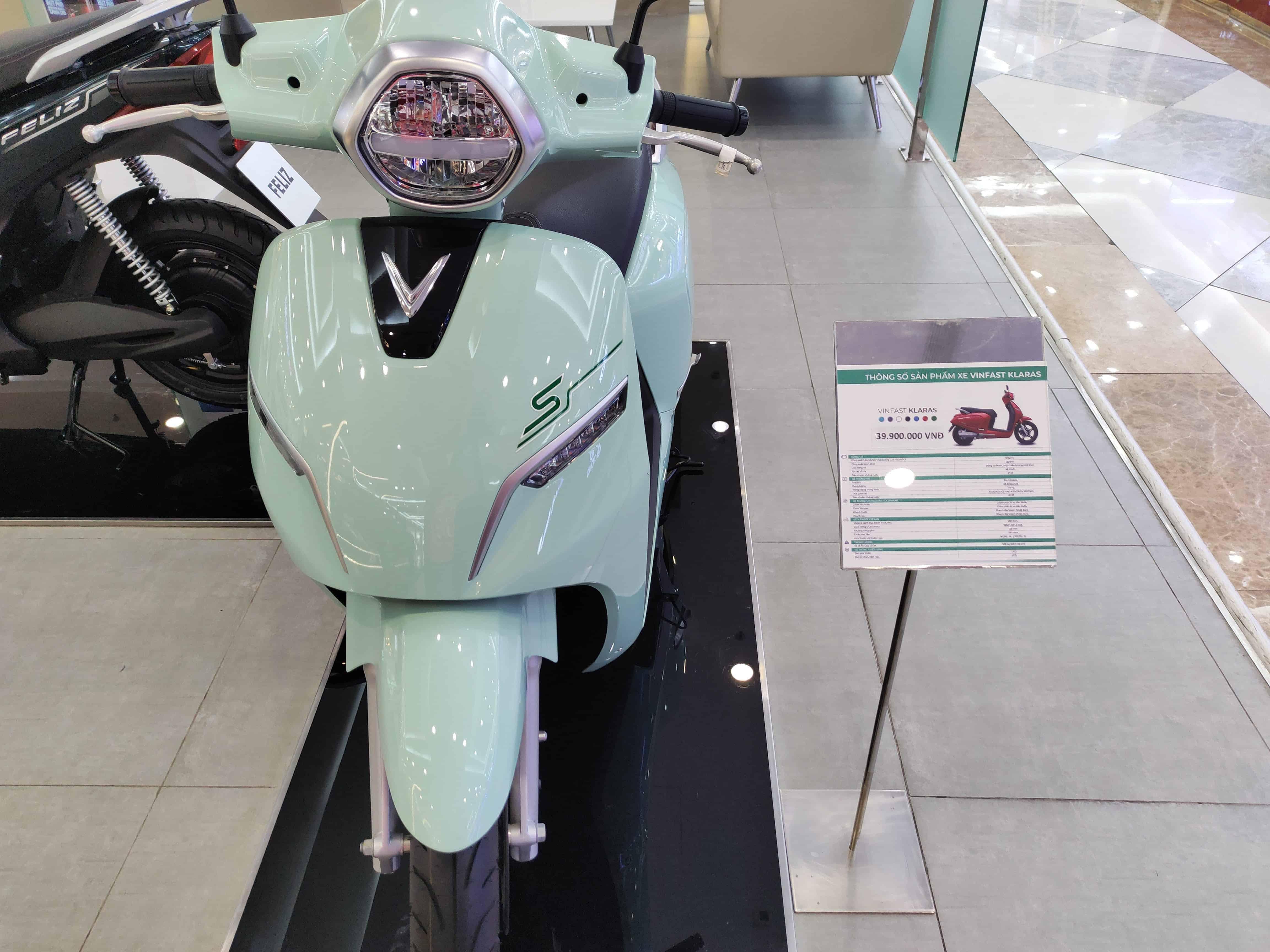Xe máy điện VinFast KlaraS màu xanh ở showroom trưng bày xe và bảng thông số kĩ thuật xe bên cạnh