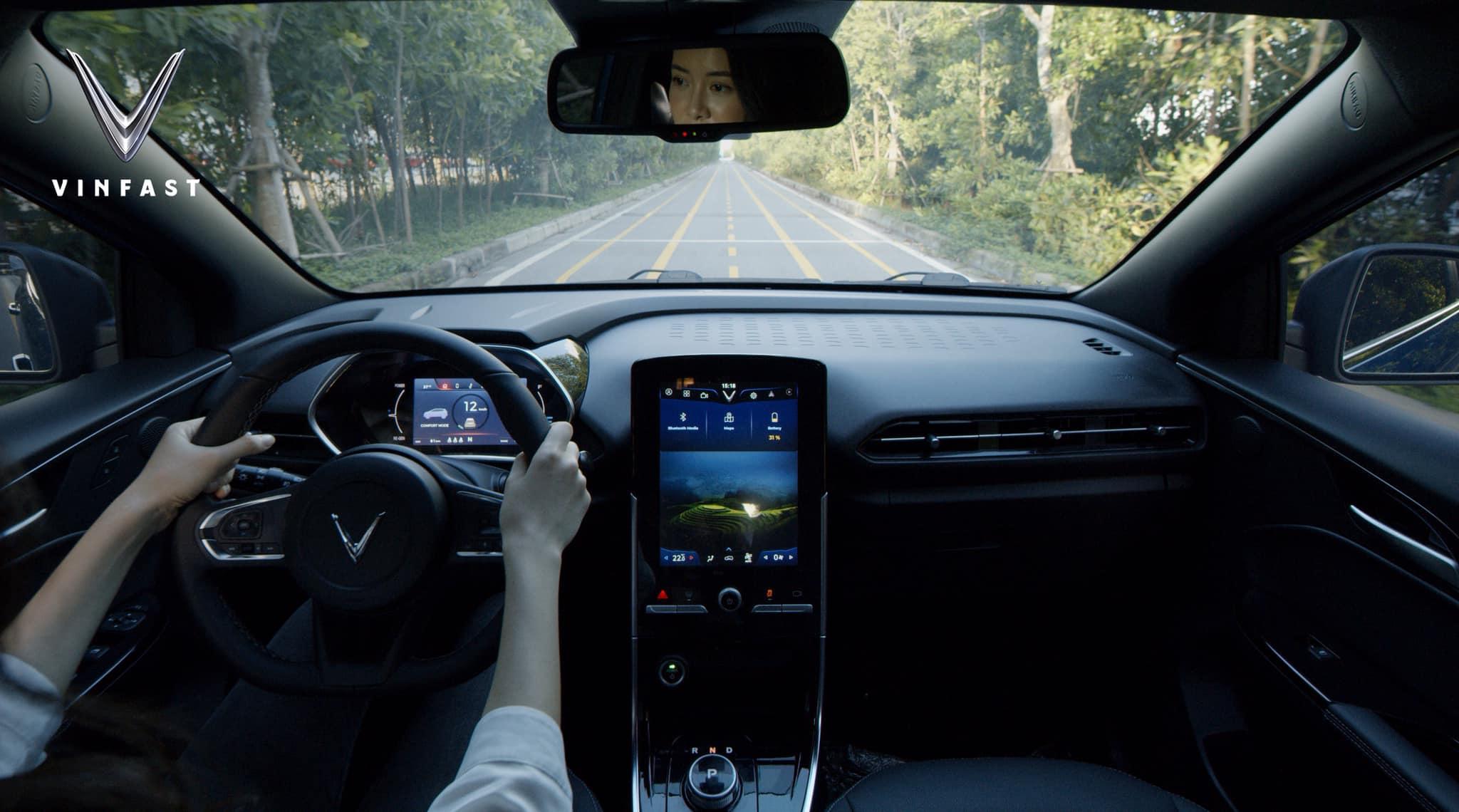 Nội thất khoang trước của xe điện VinFast VF E34 với người phụ nữ đang điều khiển xe