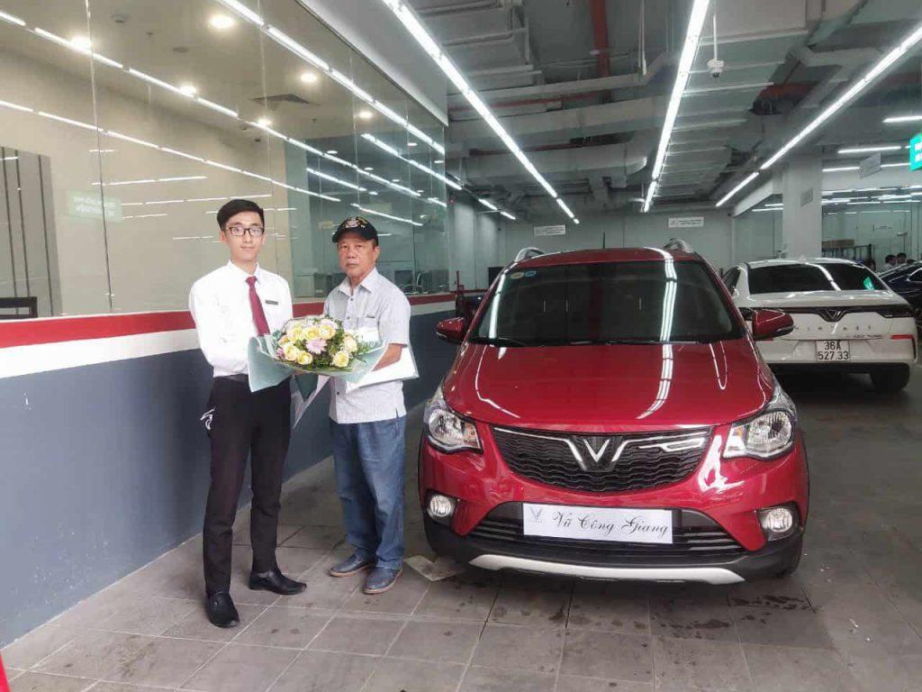 nhân viên kinh doanh đẹp trai đang tặng bông cho khách hàng nhận xe vinfast fadil