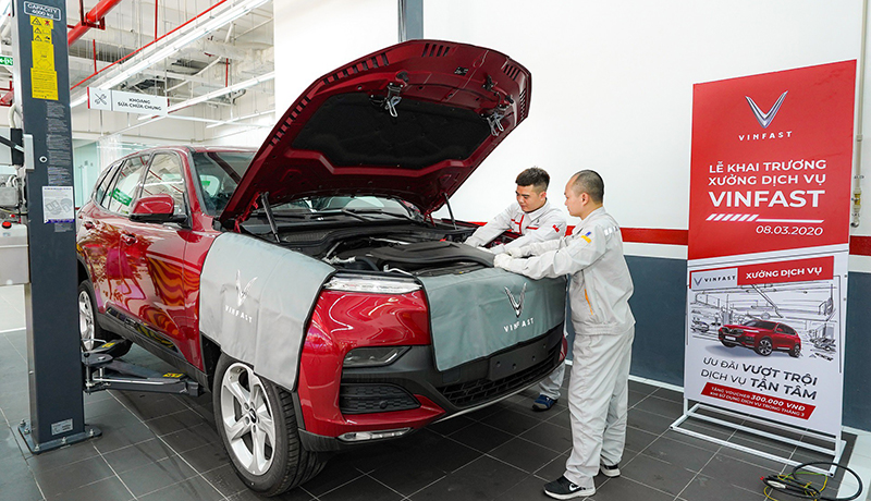 nhân viên kĩ thuật vinfast đang bảo hành xe vinfast lux sa2.0 màu đỏ tại xưởng dịch vụ chính hãng